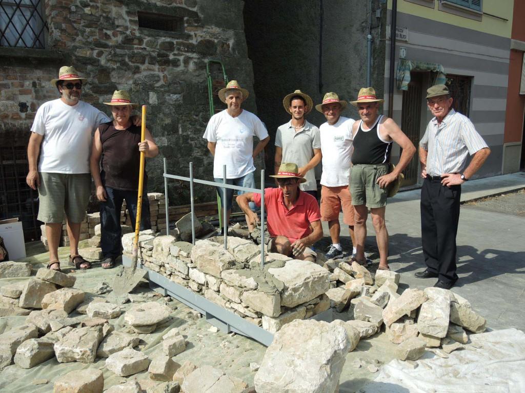 I muratori realizzano un muro in sassi